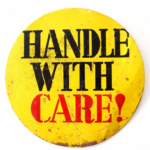 Vintage metal pinback button Handle with care